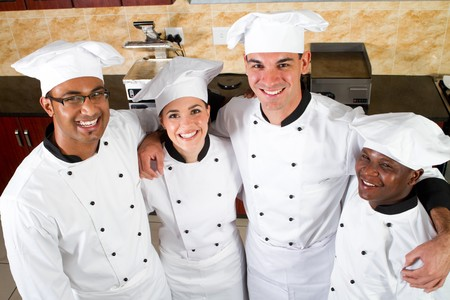 group of young happy chefs in kitchen
