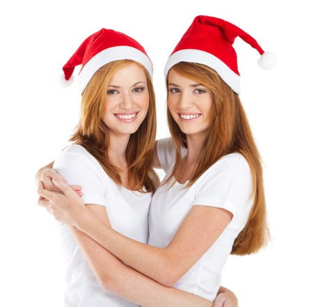 pretty sisters wearing christmas hatsの写真素材