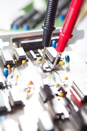 Multimeter examining a circuit board
