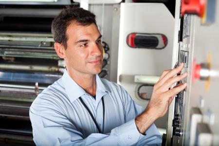 male technician setting industrial machine in modern factory