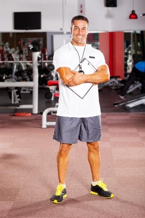 handsome male gym trainer portrait inside gym