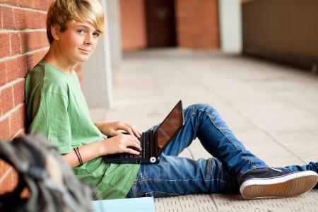 teen student using laptop in school passage
