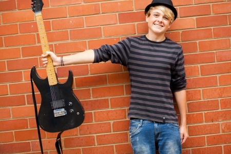 cute teen musician holding guitar