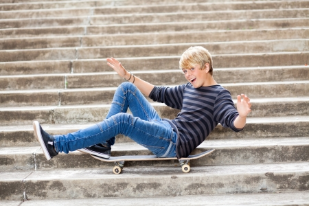 playful teen boy sitting on skateboard