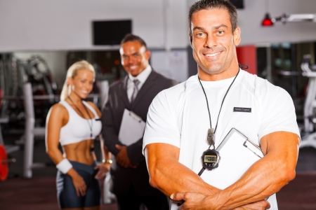 muscular senior gym trainer portrait with colleagues in background