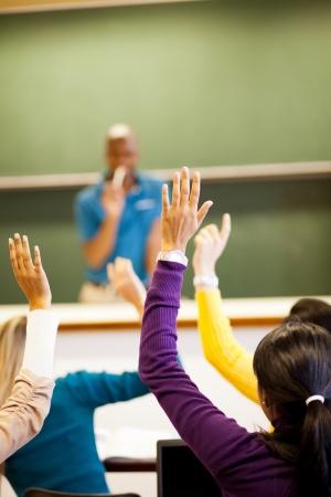 Foto de group of students arms up in classroom - Imagen libre de derechos
