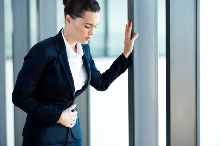 young businesswoman having stomach ache in office