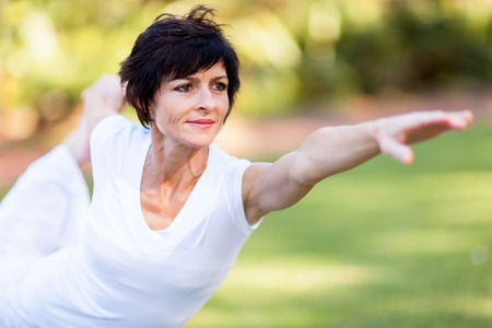 healthy middle aged woman stretching outdoors