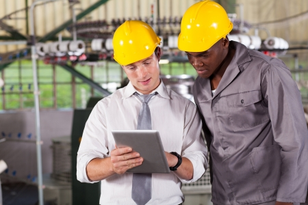 factory manager and worker looking at tablet computer