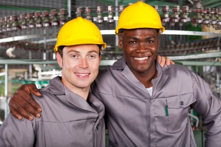 two friendly industrial workers colleagues in factory