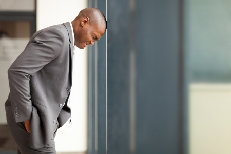 stressed african american businessman bang hi head against wall