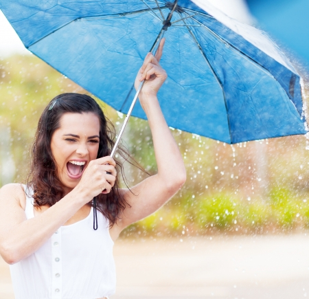 playful young woman holding umbrella in the rainの写真素材