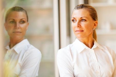 Photo pour elegant middle aged businesswoman standing by office window - image libre de droit