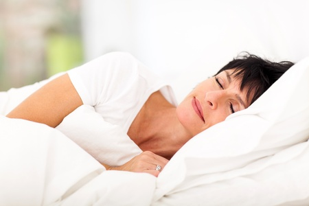 cute mature woman sleeping on bedの写真素材