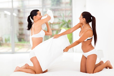 two girl friends having pillow fight in bedroom