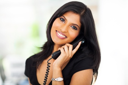 Foto de beautiful career woman talking on telephone in office - Imagen libre de derechos