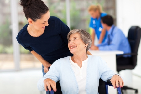 loving adult daughter accompanying senior mother to visit doctor