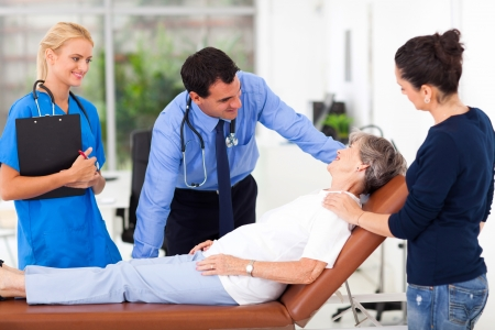 friendly male doctor talking to senior patient before examining