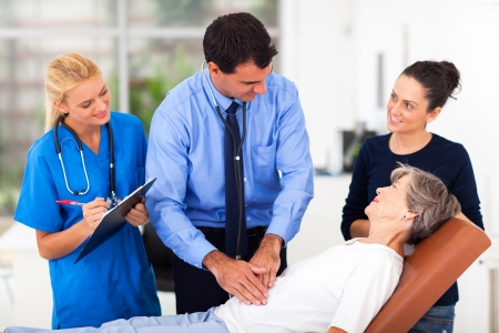 handsome medical doctor examining senior patient on examining bed