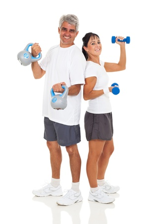 cheerful senior couple posing with various gym equipment on white background