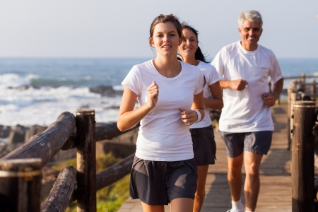 happy healthy family jogging on the beach in the morning