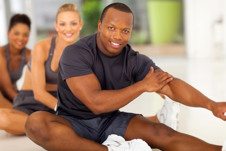 happy african man with team stretching before exercise