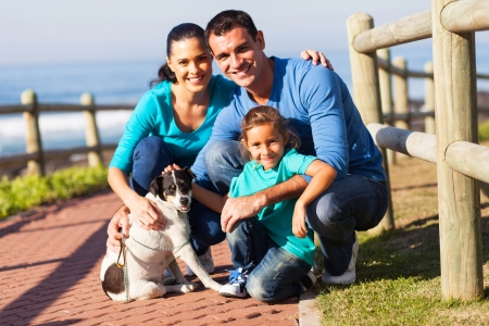 portrait of lovely family and pet dog outdoors at beach