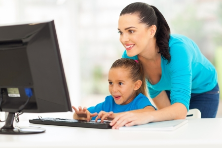 happy young mother teaching daughter computer at home