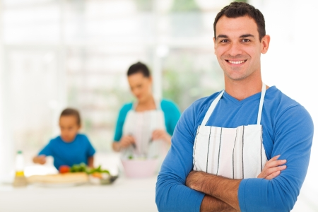 handsome family man standing in front of family in kitchen