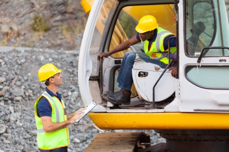 Photo pour cheerful construction foreman talking to excavator operator - image libre de droit