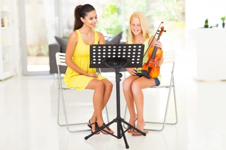 beautiful young pretty girl having violin lesson at home
