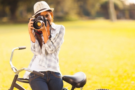 smiling young woman using a camera to take photo outdoors at the park
