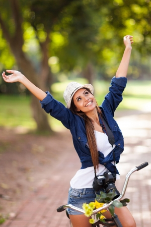 Photo for carefree young woman arms open on her bike outdoors - Royalty Free Image