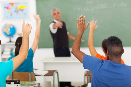 Photo pour group of students with hands up in classroom during a lesson - image libre de droit