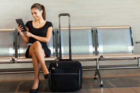 Photo pour beautiful young woman using tablet computer at airport - image libre de droit