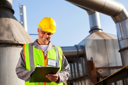 smiling senior petrochemical engineer recording technical data on clipboard
