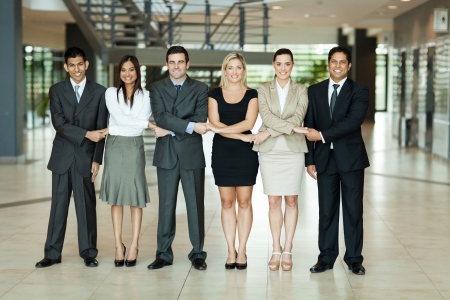 Photo pour cheerful group of business people holding hands - image libre de droit