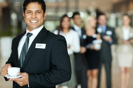 Foto de handsome indian businessman having coffee break during seminar - Imagen libre de derechos