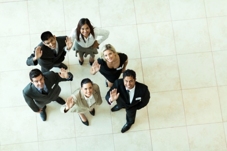 overhead view of businesspeople looking up and waving