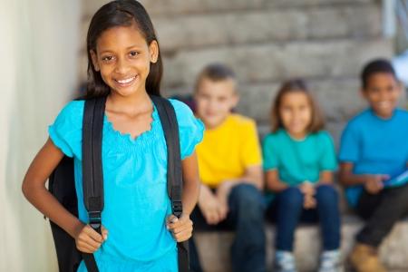 portrait of beautiful elementary school girl with schoolmates on background
