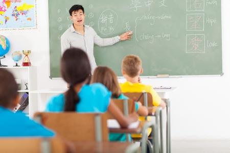 elementary school teacher teaching chinese language in classroom