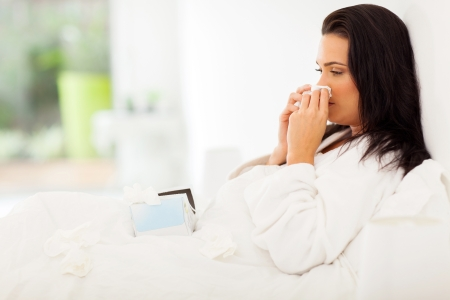 sick woman in bed blowing her nose
