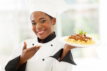 beautiful afro american chef presenting spaghetti