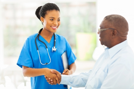 friendly african american medical nurse handshaking with senior patient