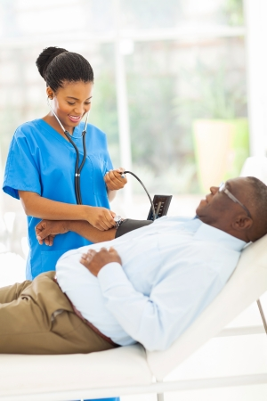 friendly young african doctor checking senior patient's blood pressure