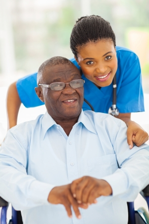 elderly african american man and caring young caregiver at home