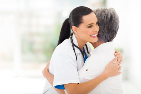 caring young medical doctor hugging senior patient