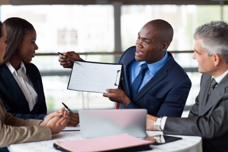 Photo pour handsome young african american businessman presenting figures at a meeting with team - image libre de droit