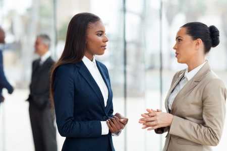 successful female colleagues having conversation in office
