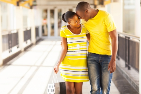 happy afro american couple flirting in shopping mall